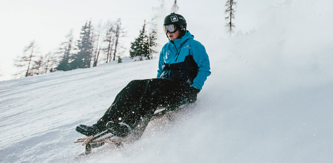 Mann auf dem Pistenbock während der rasanten Abfahrt in der Skiarena Silbersattel im Thüringer Wald
